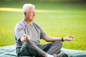 Senior man (60s) meditating, in lotus pose.