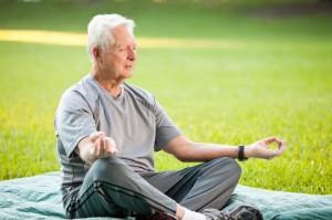 Senior man (60s) meditating, in lotus pose.