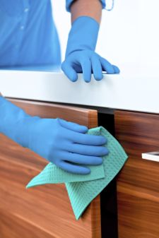 Close up of woman's arms cleaning and polishing kitchen cabinets.