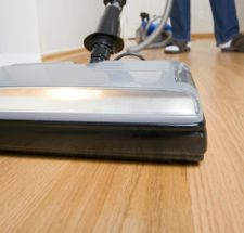 Cleaning chores: vacuuming hardwood floor. Wide angle.