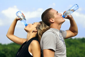 man and woman drinking water while working out
