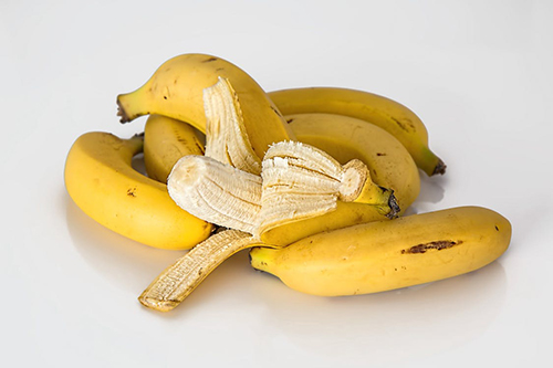 a pile of bananas, one peeled
