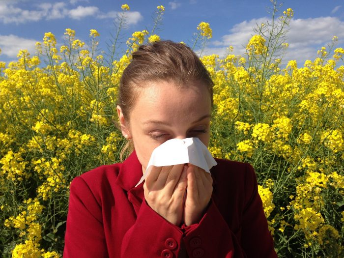 woman with asthma and allergies sneezing