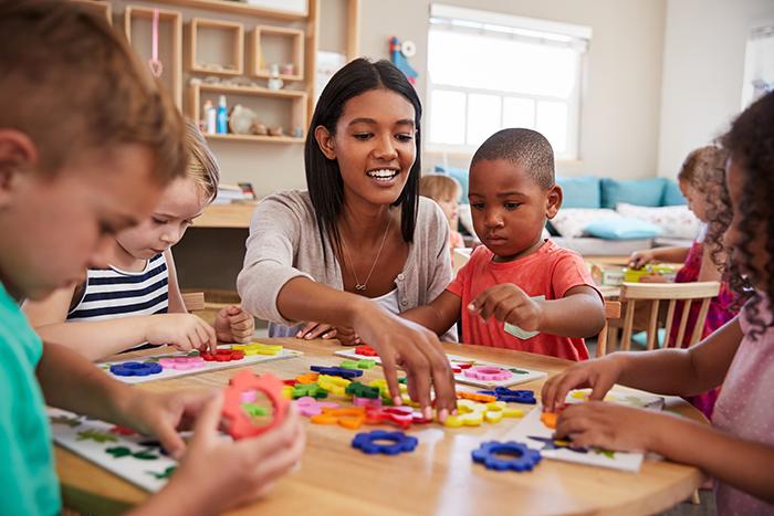 children and teacher play at preschool