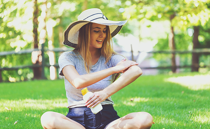 woman in hat sits outdoors and applies sunscreen to arm